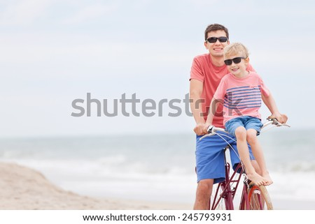 happy family of father and son enjoying their time together while biking at the beach - stock photo