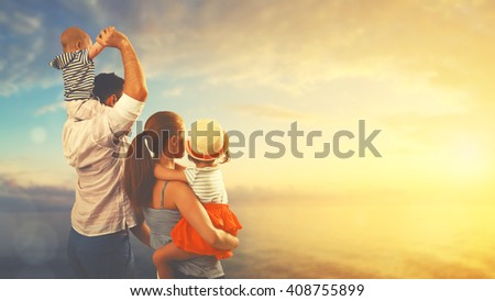 happy family of father, mother and two children, baby son and daughter on  the beach at sunset - stock photo