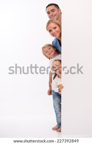 Happy family of father mother son and daughter smiling  looking  out wall  isolated on white background with copy place
