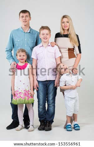 Happy family of five people, youngest son looks up in the studio - stock photo
