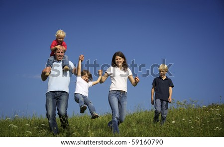 Happy family of five walking in meadow and tossing up daughter. - stock photo