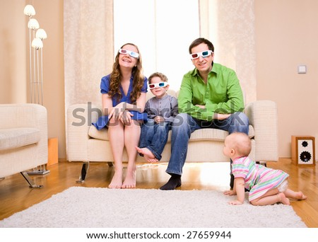 Happy family of four at home watching movie in 3D glasses.