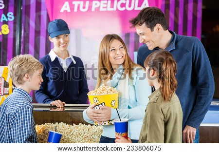Happy family of four buying snacks from female seller at concession stand in cinema - stock photo