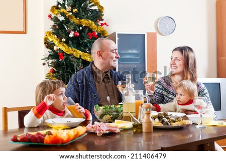 Happy family of four celebrating Christmas over celebratory table at home interior