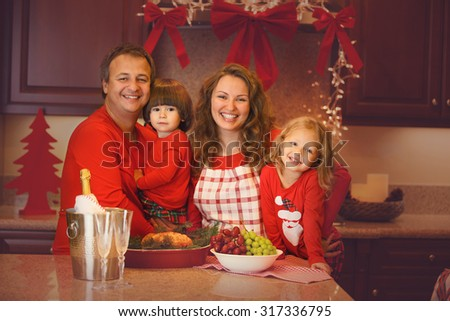 Happy family of four celebrating New Year, Christmas or Thanksgiving day with baked turkey. Mother, father, children with Christmas pajamas.  - stock photo