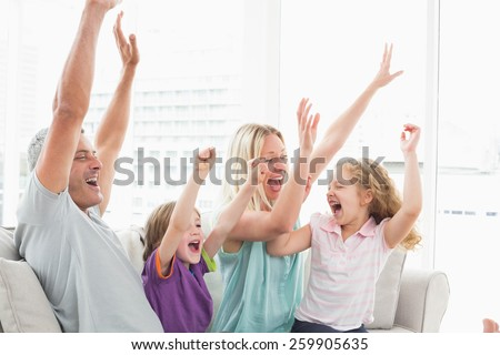 Happy family of four celebrating success while watching TV at home - stock photo