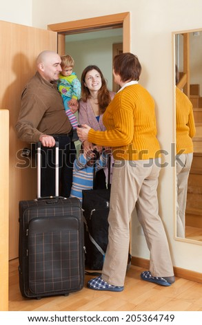 Happy family of four coming to grandmother  home - stock photo