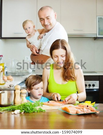 Happy family of four cooking red fish at home