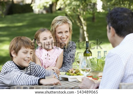 Happy family of four enjoying food and drink at table in park - stock photo