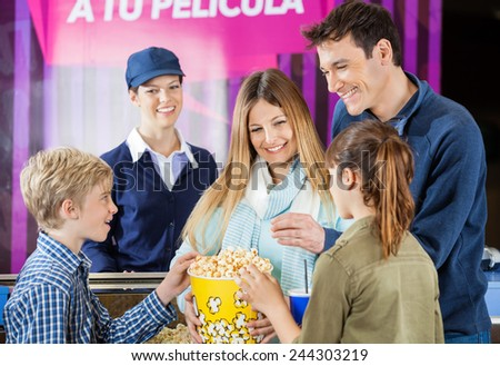 Happy family of four enjoying popcorn while female worker standing at cinema concession counter - stock photo
