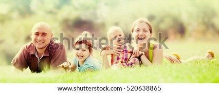 Happy family of four enjoying time at green grass