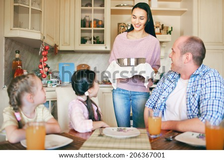 Happy family of four going to have meal in the kitchen - stock photo