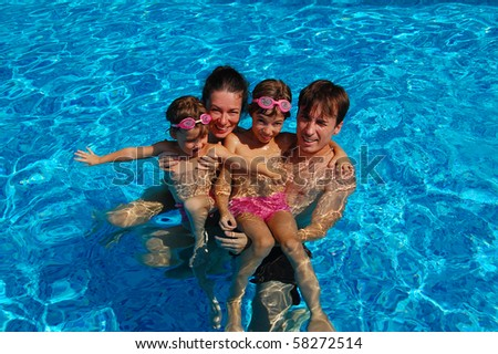 Happy family of four having fun in the swimming pool - stock photo