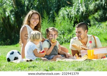 Happy family of four having picnic at countryside  - stock photo