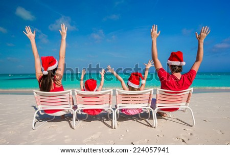 Happy family of four in Christmas Hats during tropical vacation - stock photo