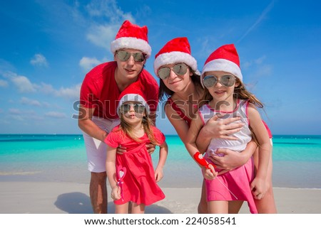 Happy family of four in Christmas Hats on white beach - stock photo