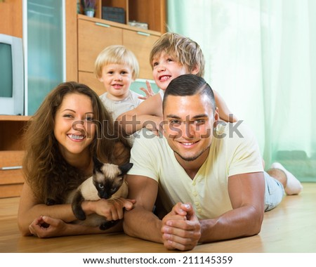 Happy family of four laying on floor with kitten in living room. Focus on girl