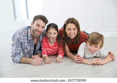 Happy family of four laying on the floor - stock photo