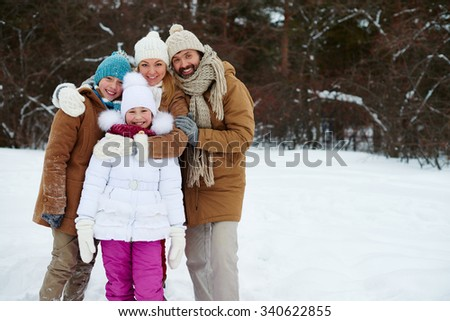 Happy family of four looking at camera in winter park - stock photo