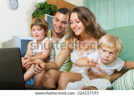 Happy family of four looking laptop on sofa in home - stock photo