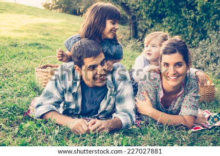 Happy family of four lying in the grass in autumn after picking apples. Warm effect added. - stock photo