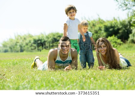Happy family of four lying on grass in sunny summer park