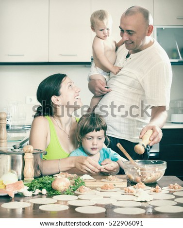 Happy family of four making fish dumplings (pelmeni) at home kitchen
