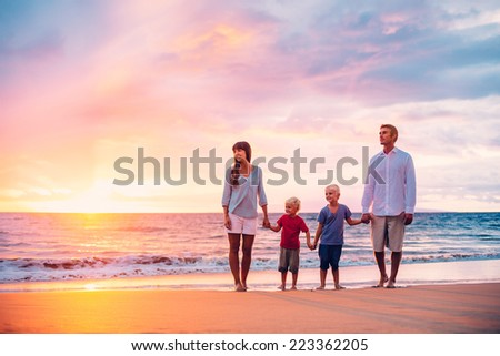 Happy Family of Four on the Beach at Sunset - stock photo
