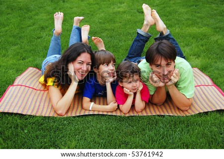Happy family of four on the grass - stock photo