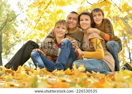 happy family of four people relaxing in a park in autumn - stock photo