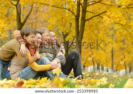 happy family of four people relaxing in a park in autumn