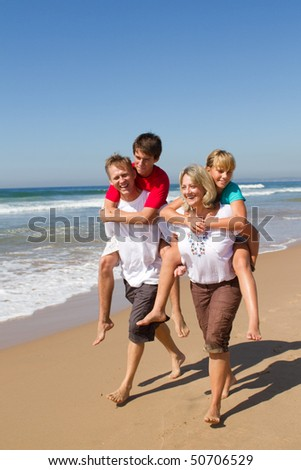 happy family of four piggyback on beach