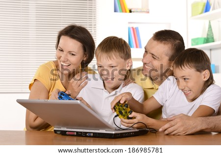 Happy family of four playing on laptop at table