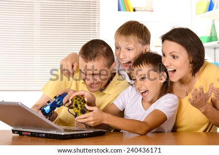 Happy family of four playing on laptop at table - stock photo