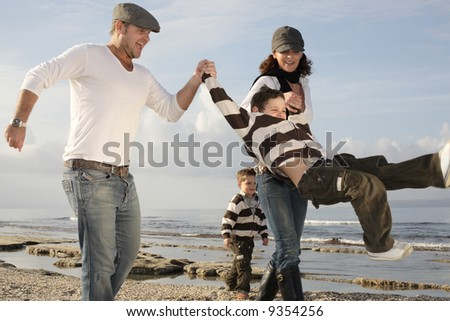 happy family of four playing on the beach - stock photo