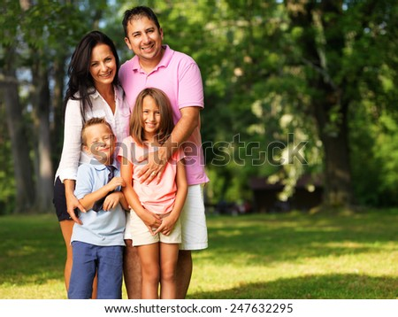 happy family of four posing outside - stock photo