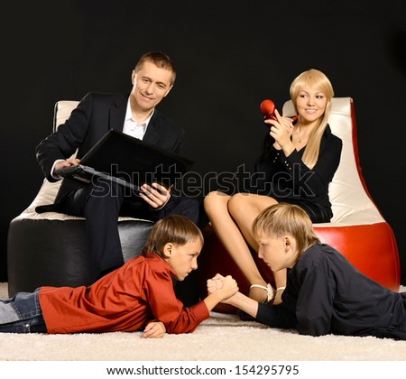 Happy family of four resting isolated on black - stock photo