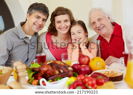 Happy family of four sitting at festive table on Thanksgiving day - stock photo