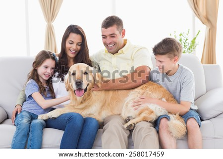 Happy family of four stroking Golden Retriever in living room - stock photo
