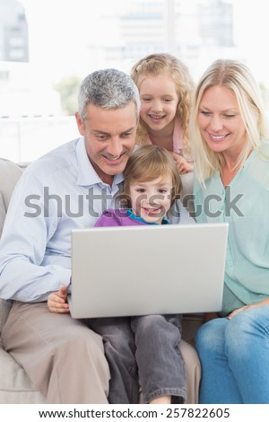 Happy family of four using laptop at home - stock photo