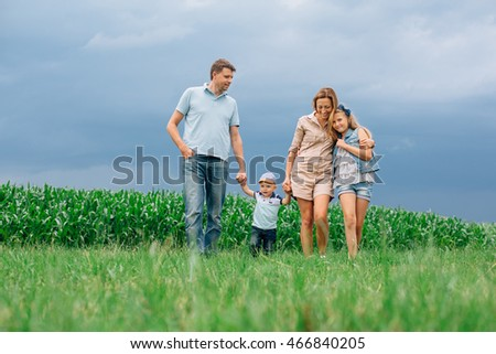 Happy family of four walking through the field. Mother father son daughter Smiling and laughing. Girl with parents and her little  brother