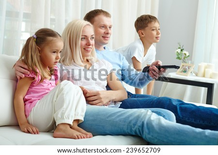 Happy family of four watching TV together on weekend - stock photo