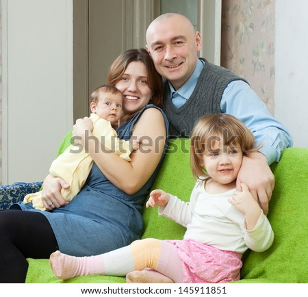 Happy family of four with newborn baby at home interior