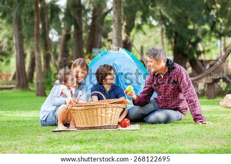 Happy family of four with picnic basket at campsite - stock photo