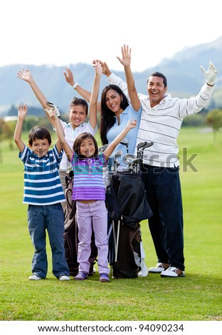 Happy family of golf player with arms up at the course - stock photo