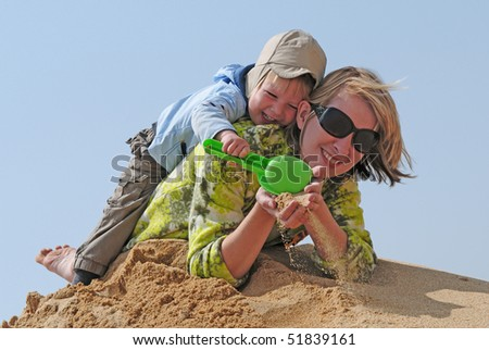 happy family of kid and mother  playing with the sand on the beach - stock photo