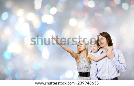 Happy family of mother father and daughter against bokeh background - stock photo