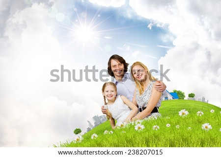 Happy family of mother father and daughter sitting on grass - stock photo