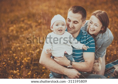 Happy family of mother father and lovely daughter in sunset light.  - stock photo