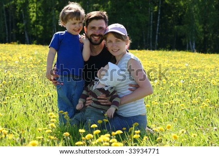Happy family of mother, father and two sons in dandelion field